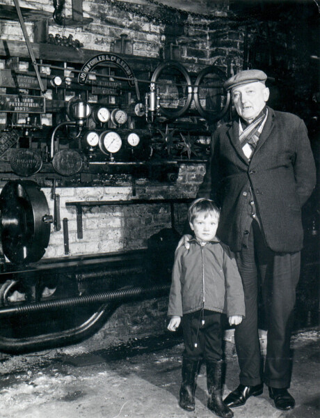 Walter James Seward, eldest son of Jim Seward, with his grandson Barry Wakelin in the workshop, Chapel Street. Circa 1969